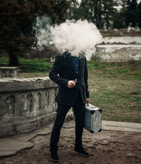 Man exhaling smoke while standing on footpath against trees
