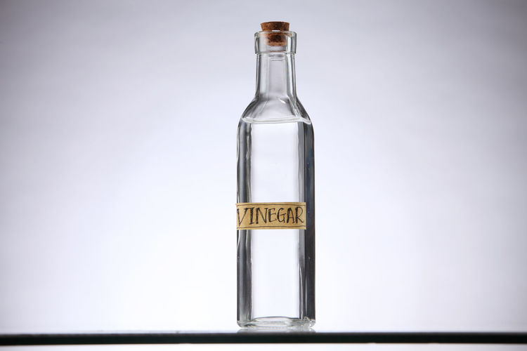 white vinegar on the shelf Container Cork Liquid Vinegar Bottle Acetic Bottle Closed Communication Condiment Container Copy Space Fluid Food And Drink Glass - Material Indoors  Label No People Nontoxic Organic Single Object Studio Shot Text Transparent Vinegar White Vinegar