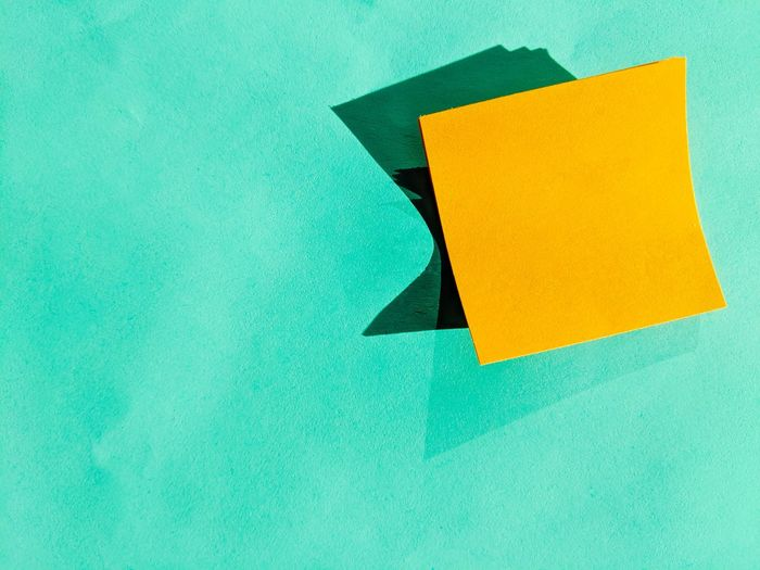 Close-up of yellow paper on wall