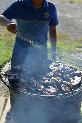 Close-up of man standing by barbecue grill