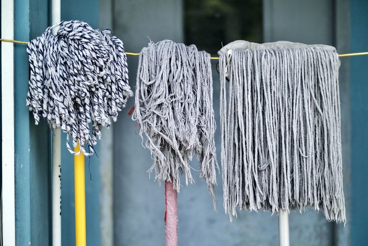 Various mops hanging on rope against building