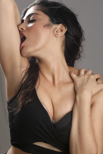 Close-up of seductive woman with eyes closed standing against gray background