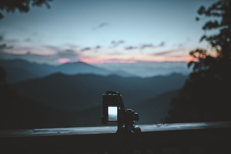 Close-up of camera on mountain against sky during sunset