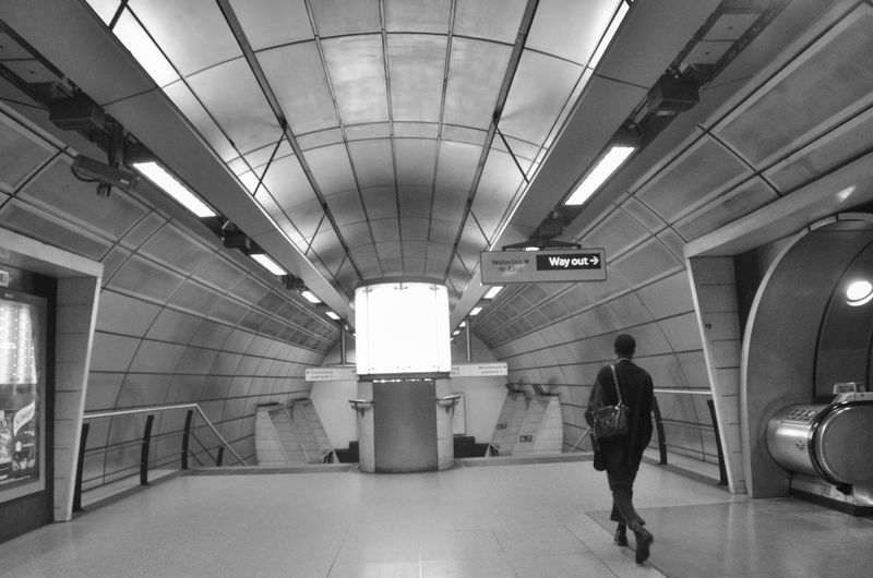Rear view of person walking in subway station