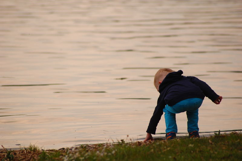 Young Boy Standing By Water
