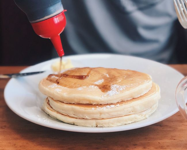 Honey pouring on pancakes in plate