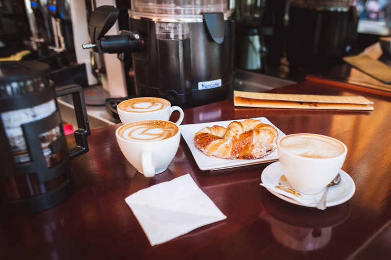 Coffee cups and croissant on table at restaurant