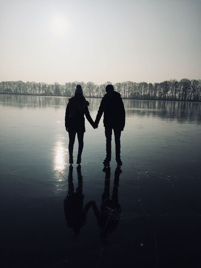 Silhouette couple holding hands while standing on ice rink against sky