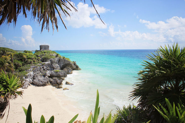 View Of Empty Beach In Tulum Against Blue Sky