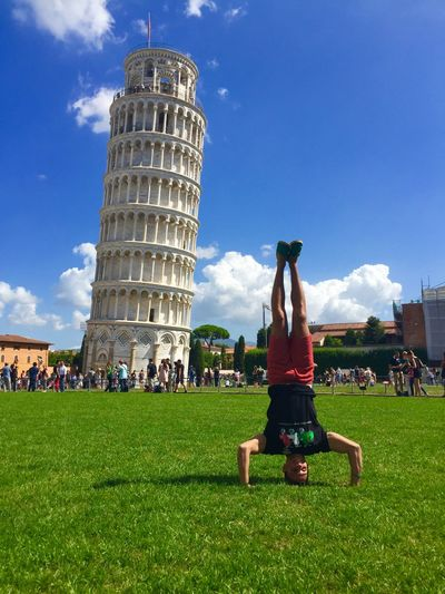 Man Practicing Headstand Against Leaning Tower Of Pisa