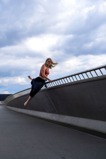 Low angle view of woman climbing on bridge against sky