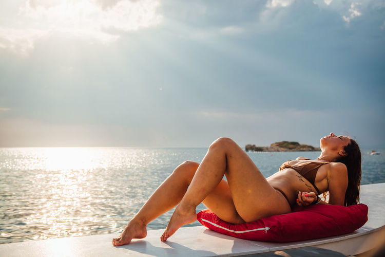 Young Adult Water Relaxation One Person Sky Lying Down Sea Young Women Sunlight Leisure Activity Nature Adult Holiday Vacations Lifestyles Trip Resting Full Length Day Horizon Over Water Beautiful Woman Outdoors