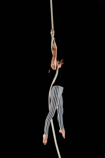 Circus Acrobat Adult Agility Arms Raised Athlete Balance Black Background Challenge Coordination Determination Effort Flexibility Full Length Hanging Holding Human Arm One Person Performance Silk Skill  Sport Strength Studio Shot Vitality