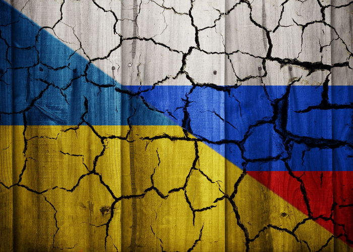 Full frame shot of cracked wall with russian and ukrainian flags