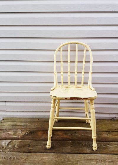 Empty Chair On Wooden Table Against Wall