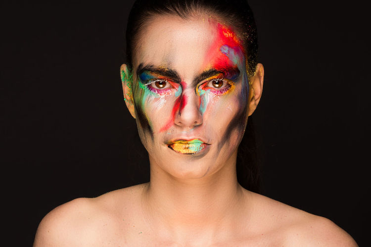 Portrait of woman with face paint against black background