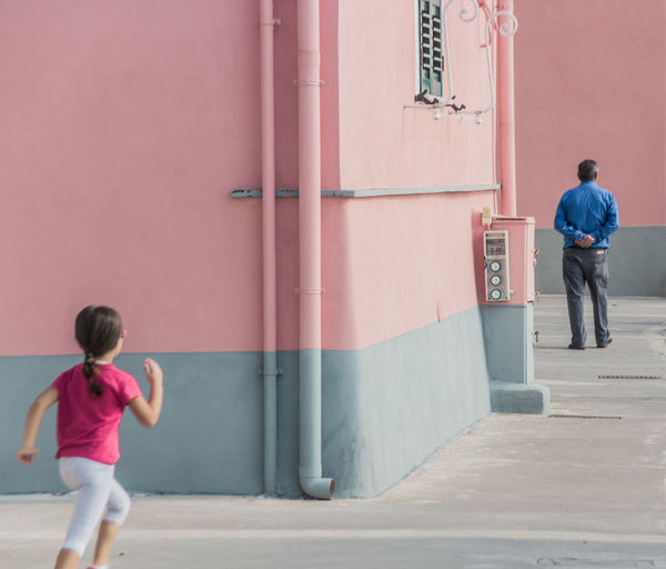 Rear view of daughter running towards father in city