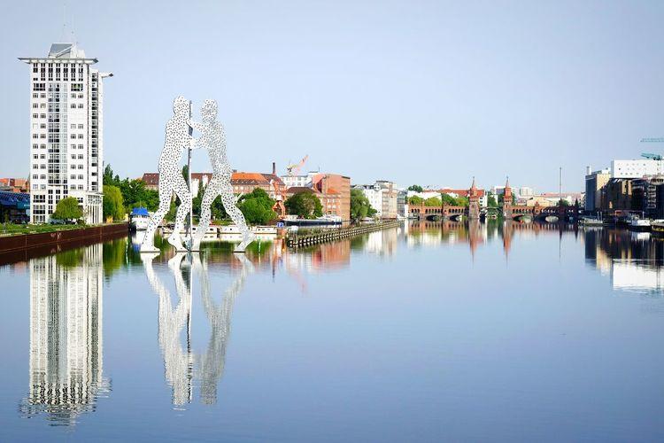 Molecule Men Statue On Spree River Against Clear Sky