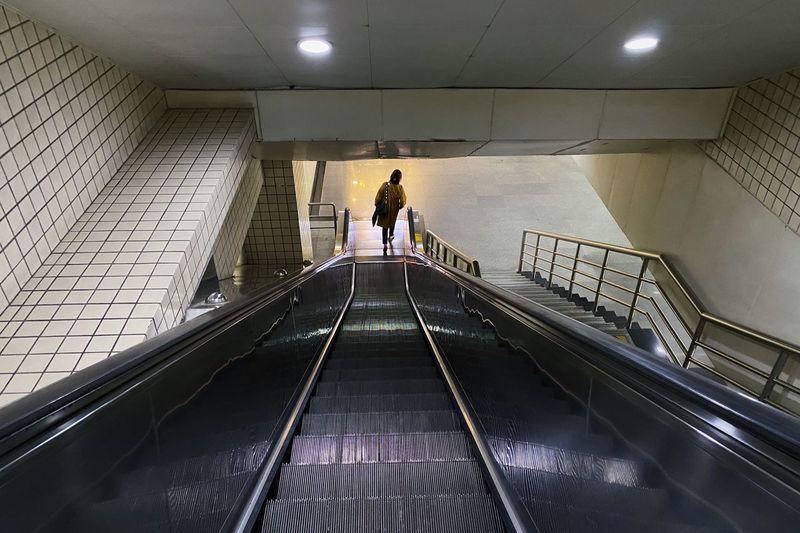 Rear view of woman on escalator