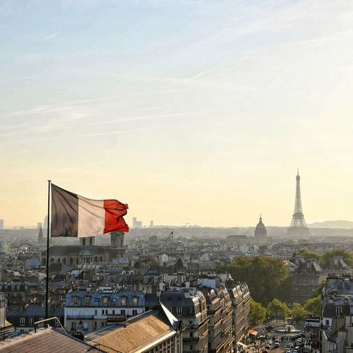 French flag against eiffel tower in city during sunset