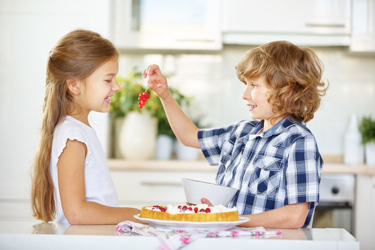 Side View Of Siblings Preparing Cake At Home