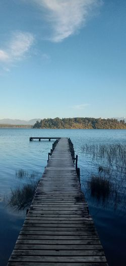 Wooden pier over lake against clear blue sky on sunny day.
