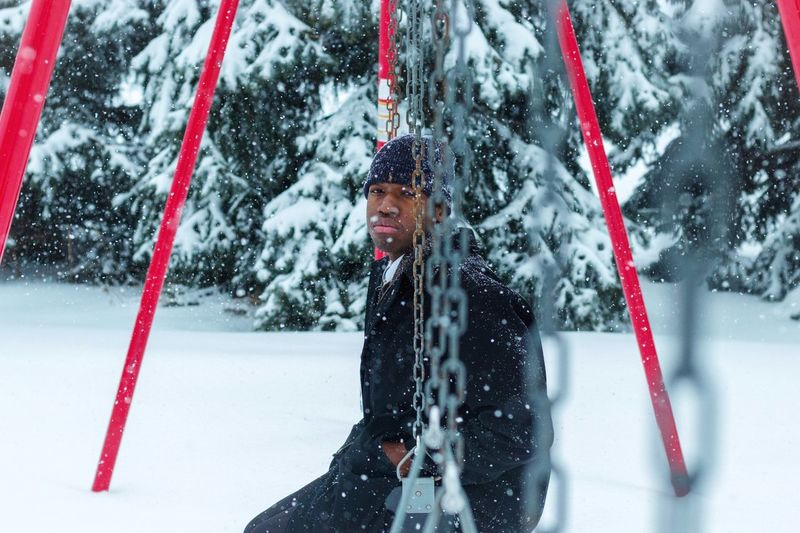 Portrait of man sitting on swing during snowfall