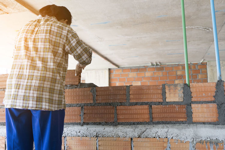 Brickman is working his the building area Brick Wall Construction Industry Lady Wall Worker Block Brick Bricklayer Brickwork  Building Cement Craft Hand Handyman House Level Mason Masonry Material Mortar Putty Repair Site Tools