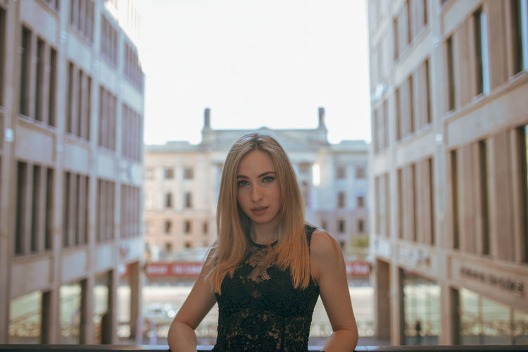 Portrait of young woman standing against buildings in city
