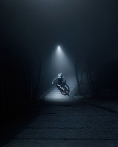 Person riding bicycle in illuminated tunnel