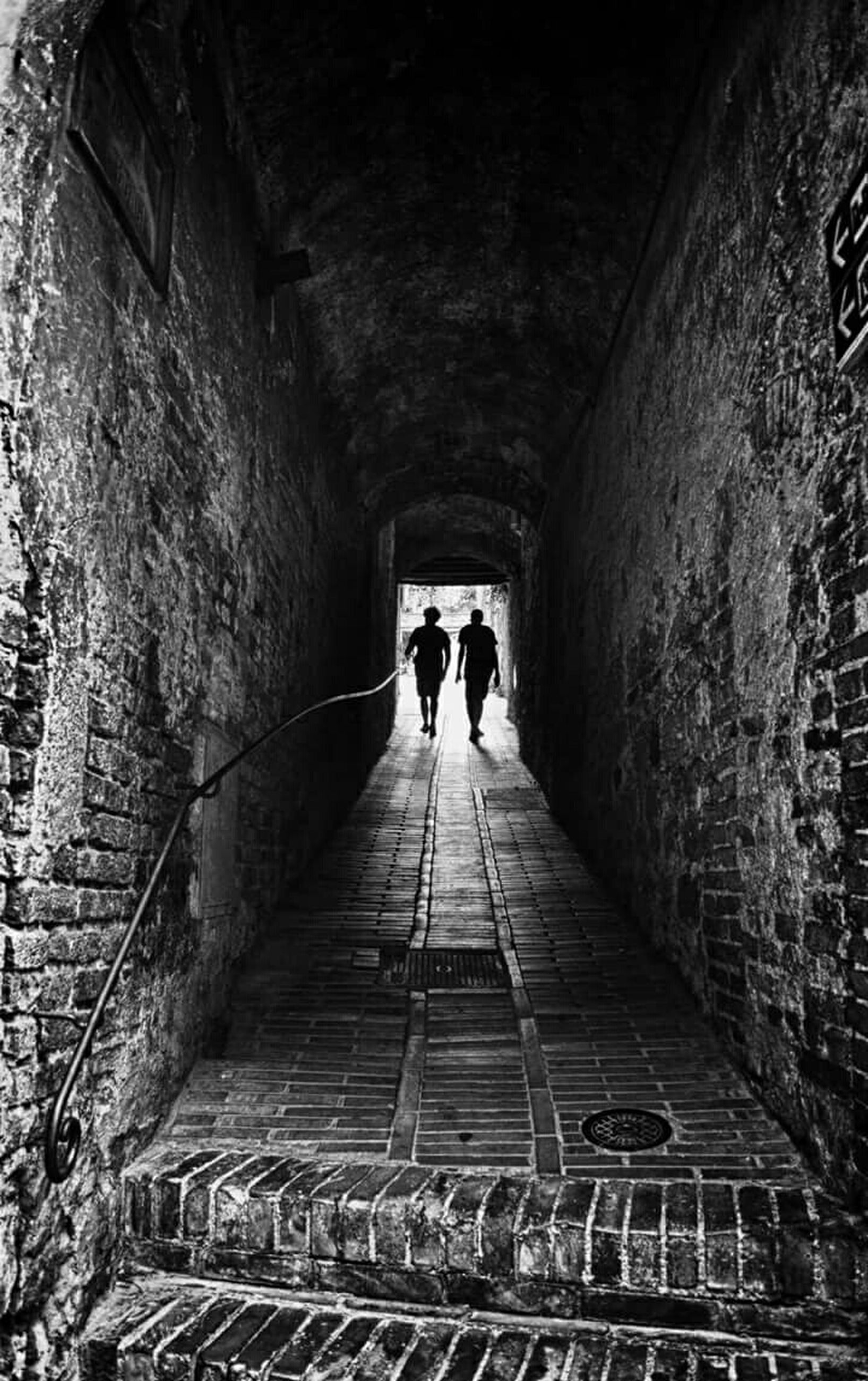the way forward, architecture, built structure, men, walking, tunnel, lifestyles, indoors, rear view, full length, diminishing perspective, person, leisure activity, vanishing point, arch, railing, wall - building feature