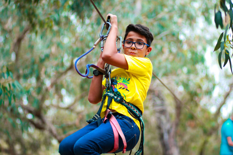 Portrait Of Teenage Boy Zip Lining At Forest