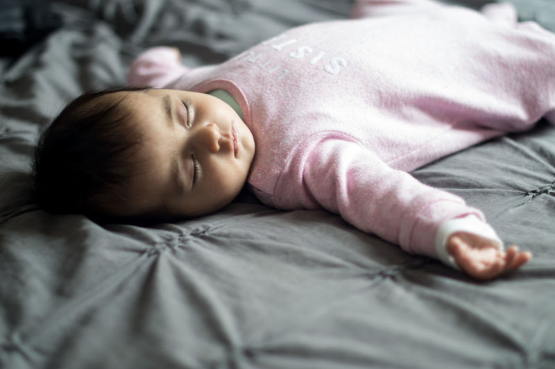 Cute baby sleeping peacefully in bed in his parents' room