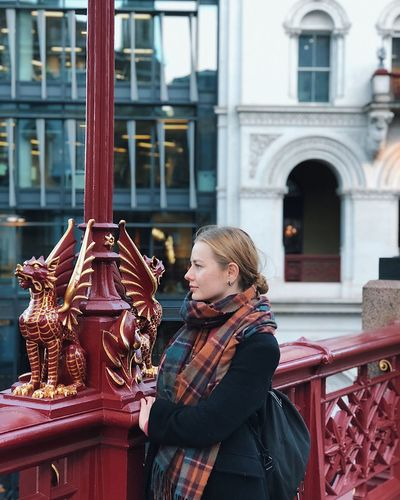 Woman looking away while standing by railing