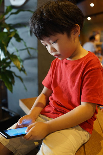 little boy using mobile phone, addicted game and cartoon Boys Casual Clothing Child Childhood Concentration Connection Indoors  Innocence Leisure Activity Lifestyles Looking Males  One Person Real People Sitting Surfing The Net Table Technology Three Quarter Length Wireless Technology