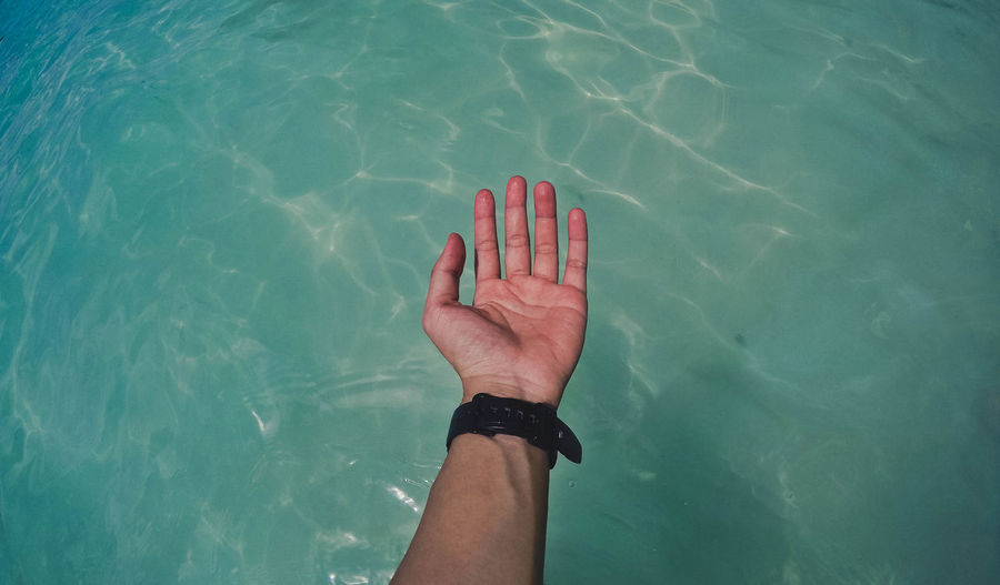 High angle view of person hand in swimming pool