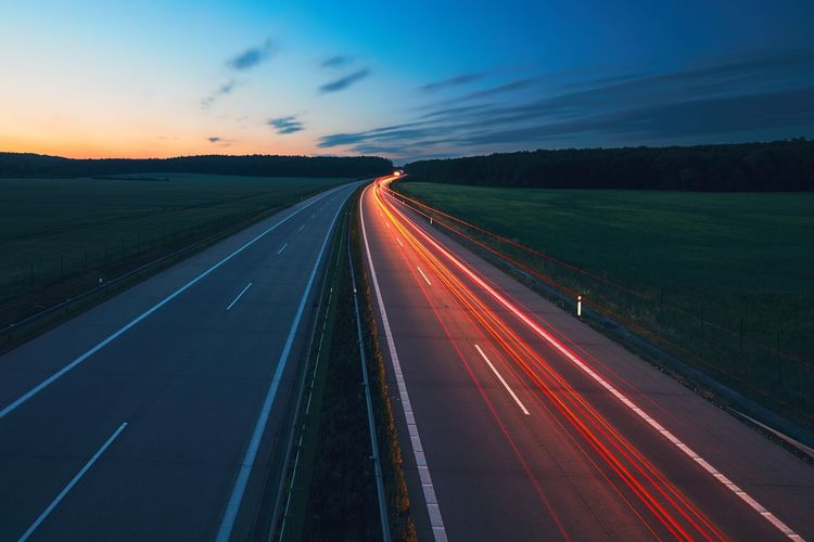 Light Trails On Road Against Sky At Sunset