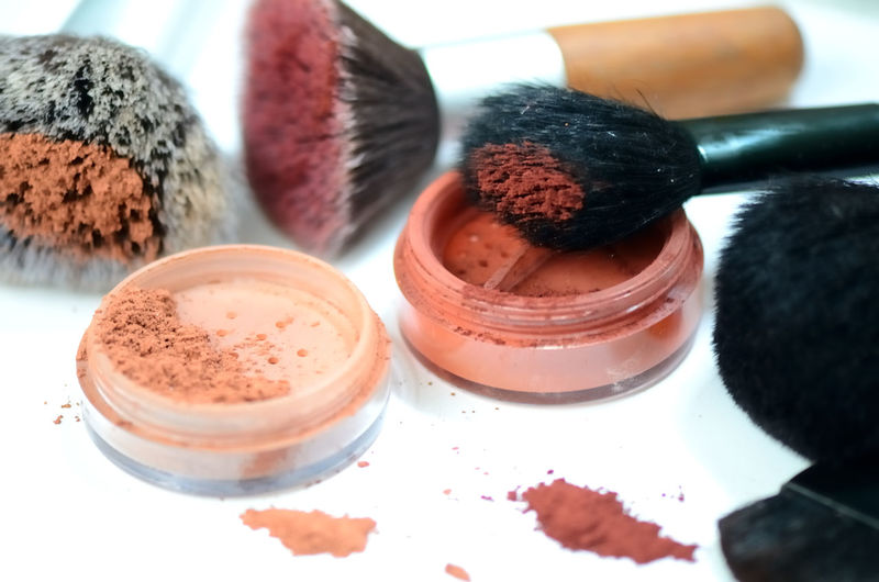 Close-Up Of Eyeshadow And Make-Up Brushes On Table
