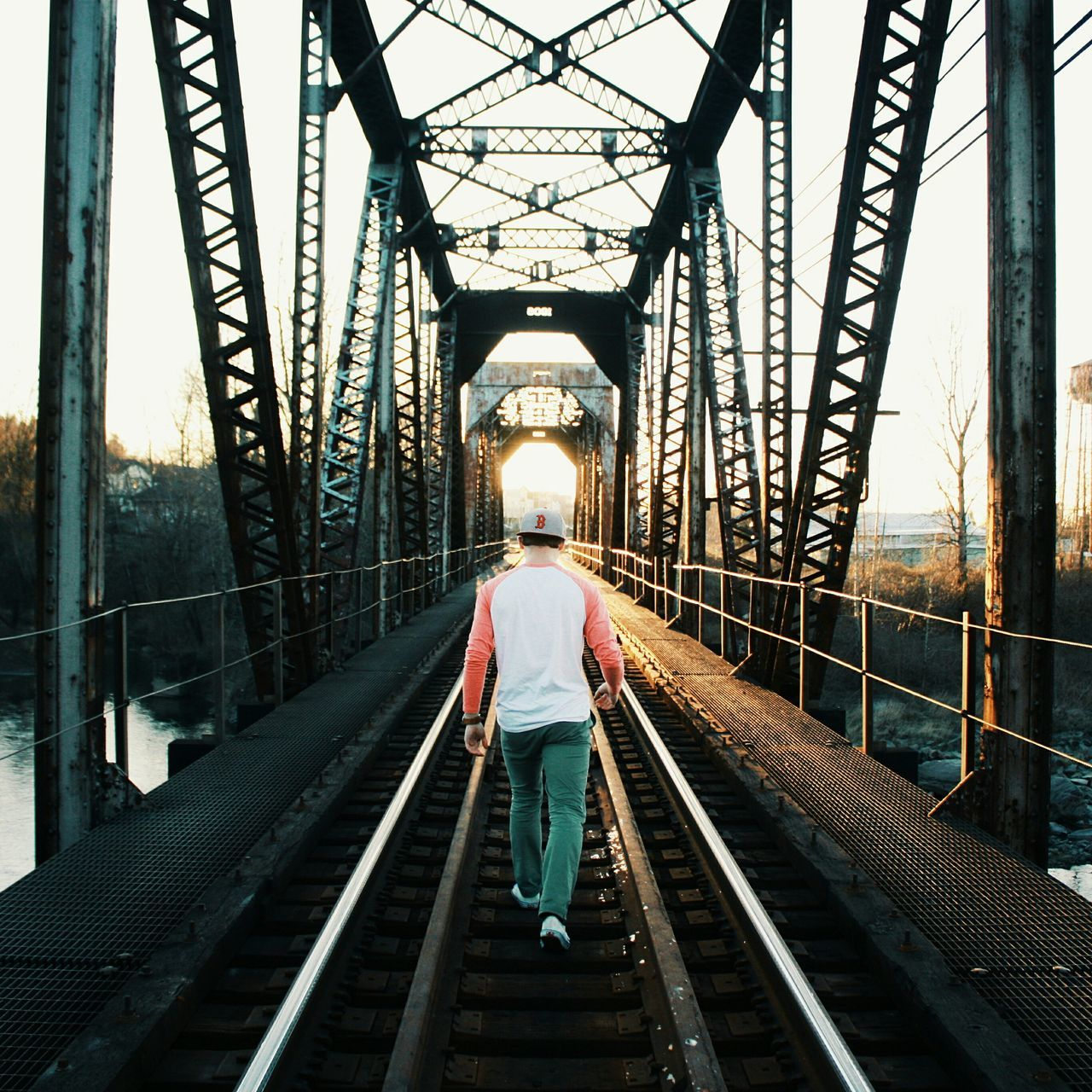 REAR VIEW OF MAN ON RAILWAY BRIDGE