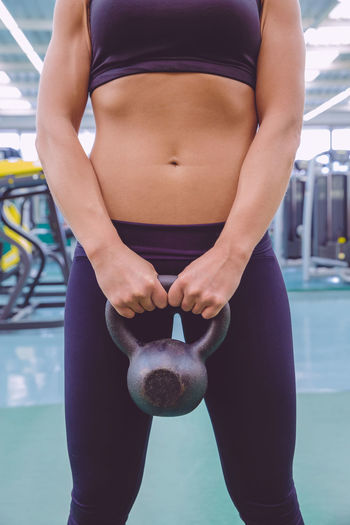 Midsection Of Woman Doing Exercise With Kettlebell At Gym