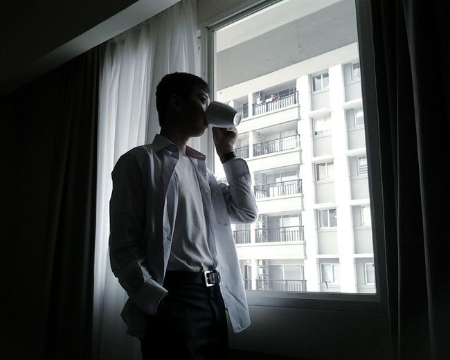Low angle view of young man drinking coffee by window in apartment