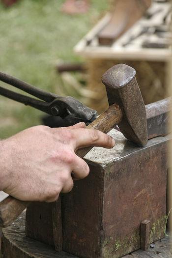 Cropped image of blacksmith using hammer