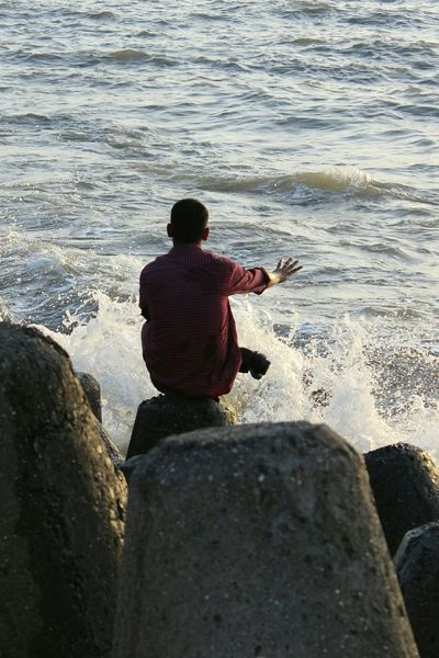 People And Places Water Leisure Activity Water Sitting Leisure Activity Rear View Person Tranquil Scene Relaxation Vacations Steps In Front Of Tourist Sea Tranquility Day Getting Away From It All Stone Material Tourism Scenics Outdoors Nature