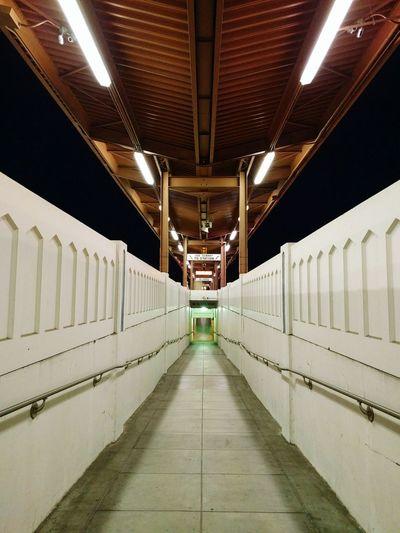 Illumianted walkway at railroad station platform during night