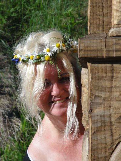 Portrait of smiling woman with flower tiara during sunny day