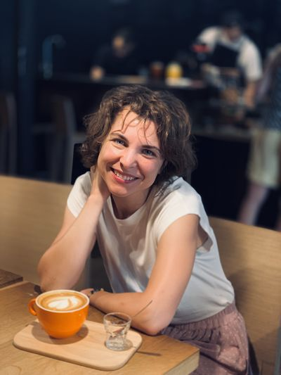 Portrait of happy woman having coffee while sitting in cafe