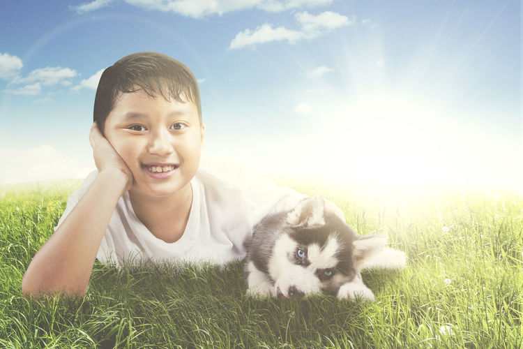 Animal Animal Themes Child Childhood Dog Domestic Domestic Animals Field Grass Innocence Looking At Camera Mammal Nature One Animal One Person Pet Owner Pets Plant Portrait Real People Sky Smiling