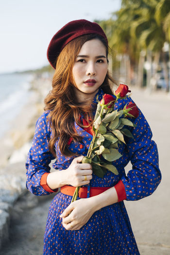 Close-up portrait of beautiful woman holding rose standing at beach