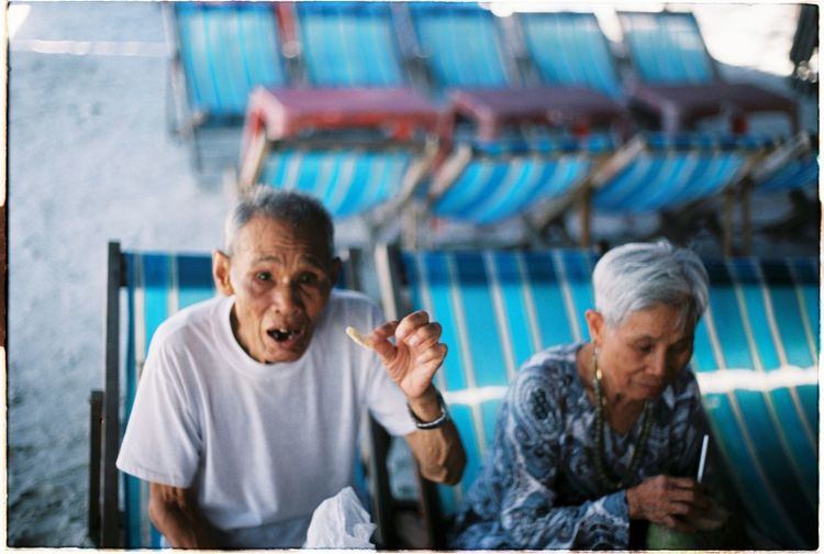 Senior People Sitting On Deck Chair While Having Food At Beach