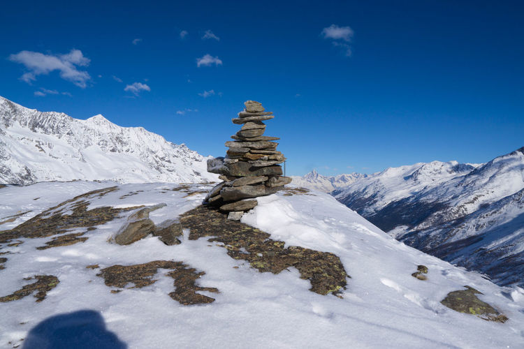 A small Cairn on the Plattjen summit station Cairn Cairns Naturephoto Main_vision Naturelovers Lookup Highaltitude Rocks Stack Landmark Liveauthentic Thecreative Mountain Saas Fee High Angle View Nature Scenery WeLiveToExplore Tranquility Adventure Winter Snowcapped Mountain Pinaceae Blue Sky Landscape Mountain Range